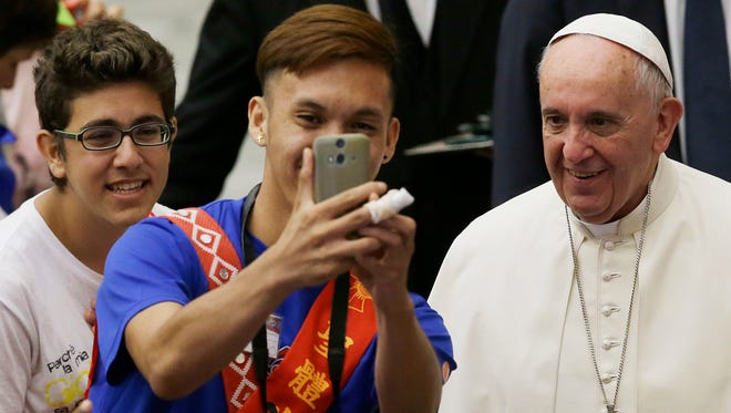 A boy takes a selfie with Pope Francis during a meeting with the the Eucharistic Youth Movement in the Paul VI hall at the Vatican.