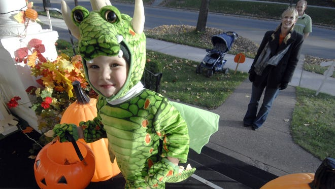 In this 2007 file photo, Jackson Culver, of Mosinee, crawls up the steps in search of candy while trick-or-treating with his mom and dad, Sarah and Tim, waiting behind on Wednesday to celebrate Halloween.
