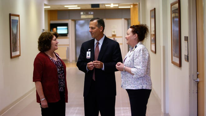 New San Juan Regional Medical Center President and CEO Jeff Bourgeois, center, talks with hospital staff outside his office on Friday in Farmington.