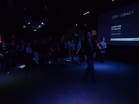 A crowd of at least 100 attendees learn to dance salsa