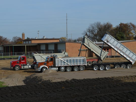 Construction crews dumping dirt outside Lansing's Fairview STEM Magnet School Friday, Nov. 18, 2016. The work at Fairview is in preparation for an expansion of the elementary school following the passage of the $120 million Pathway Promise millage.