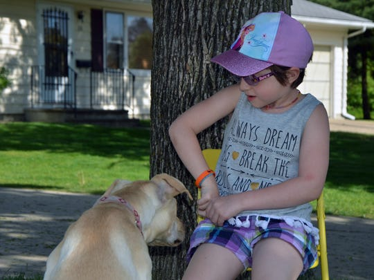 Nattaly Brown feeds her dog, Maddie, treats she hid in her front pocket Monday afternoon.