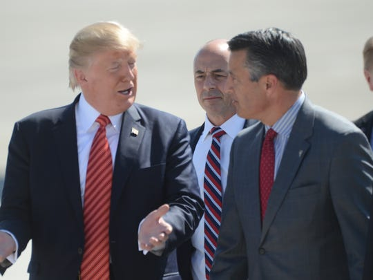 President Donald Trump talks with Nevada Gov. Brian Sandoval following his arrival to Reno on Aug. 23, 2017.