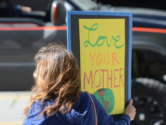 A woman holds a poster at passing traffic during a