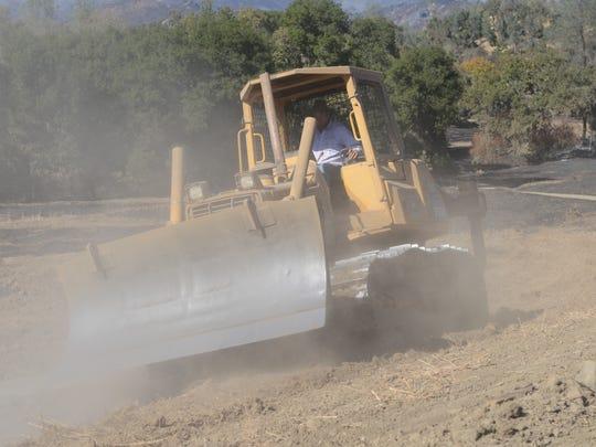 A resident of Capell Valley, Calif., runs a bulldozer