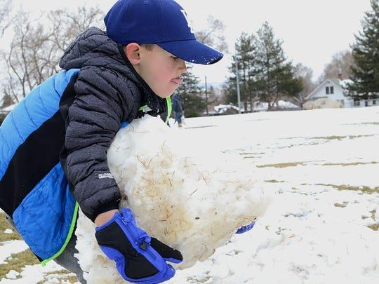 Nikolai Nelson, 6, makes a snowman at Plumas Park in Reno on March 2, 2018.