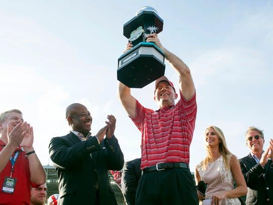 Jeff Brohm hoists the Bahamas Bowl trophy in 2014 alongside WKU athletic director Todd Stewart (far left).