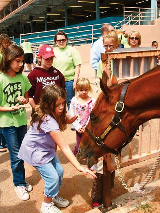 The horse gladly accepts treats during Family Day at Ruidoso Downs.