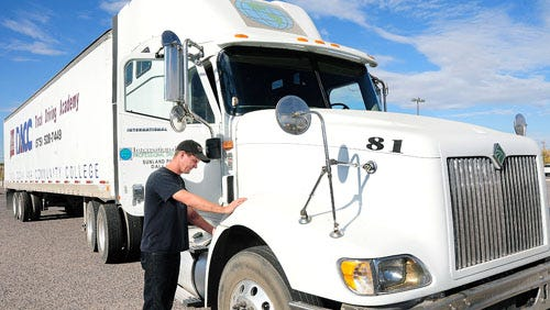 Justin Gutierrez, a student truck driver at the International Truck Driving School at Do–a Ana Community College, latches the hood of a truck.