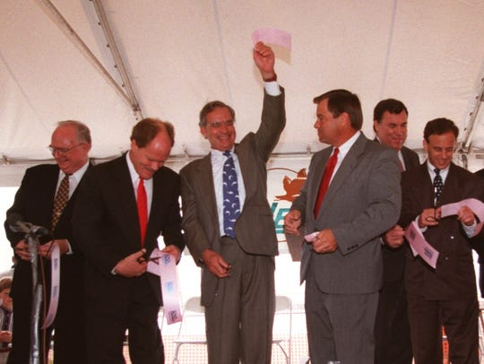 Congressman Porter Goss holds up his piece of the ribbon