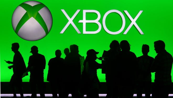 On June 10, 2014, people are silhouetted against an Xbox display at the annual E3 video game extravaganza in Los Angeles.