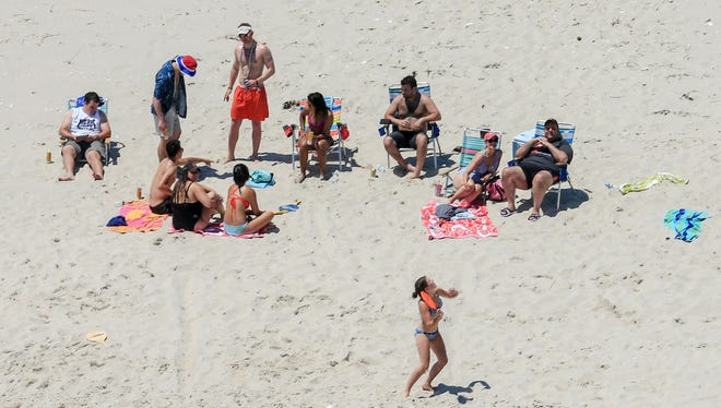 in this July 2, 2017, photo, New Jersey Gov. Chris Christie, right, uses the beach with his family and friends at the governor's summer house at Island Beach State Park.