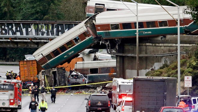 Cars from an Amtrak train spilled Dec. 18, 2017, onto Interstate 5 below alongside smashed vehicles as some train cars remain on the tracks above in DuPont, Wash.