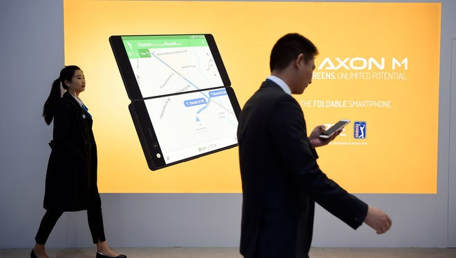A billboard announces the new ZTE dual-screen foldable smartphone AXON M on the first day of the Mobile World Congress (MWC) on Feb. 26, 2018, in Barcelona.