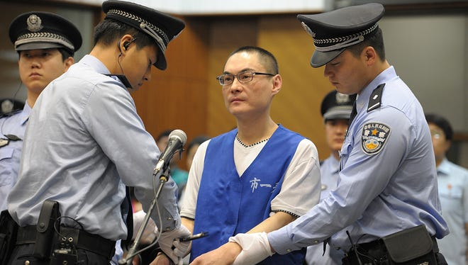 Han Lei is handcuffed by police officers after his verdict was read in a court in Beijing, China.