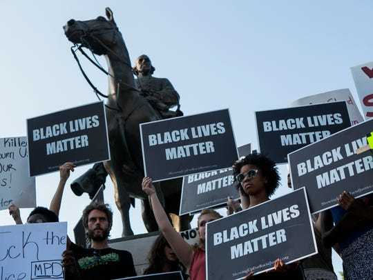 "Elechi Egwuekwe, 16, holds a ""Black Lives Matter"" sign Aug. 12, 2017, as she stands in front of the Nathan Bedford Forrest statue in Health Sciences Park during a protest showing support for those who were injured or lost their lives in Charlottesville, Virginia."
