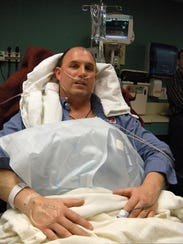 Dave Sanderson of Charlotte, N.C., lies in a hospital