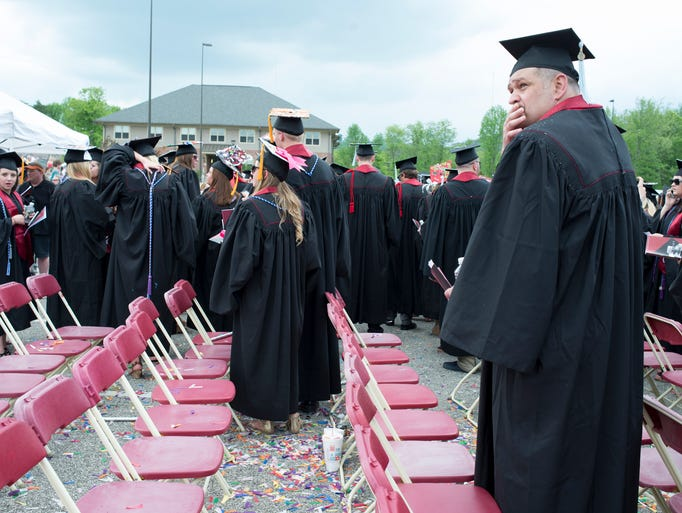 Graduates walk toward storm shelters as inclement weather approaches during Indiana Univeristy Southeast's commencement ceremony in New Albany, Ind. The ceremony was ultimately cancelled.  May 12, 2014.