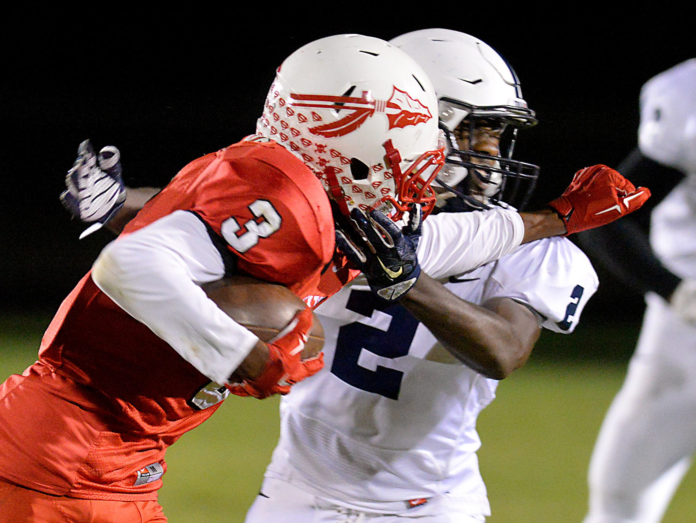 Sexton receiver Devin Taylor stiff arms East Lansing defensive back Kentre Patterson for a first down after a catch at Sexton Friday 10/9/2015.