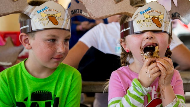 Seth Wojcik, 6, left, watches his cousin Trinity Maxey, 4, eat her cone of Moose Tracks ice cream Thursday, July 26, 2018, at Centennial Park in Fort Myers. The cousins and their siblings were among thousands who turned out to get a free scoop of ice cream in support of The Salvation Army. For every scoop given out, $1 will be donated to the local Salvation Army to support its community programs.