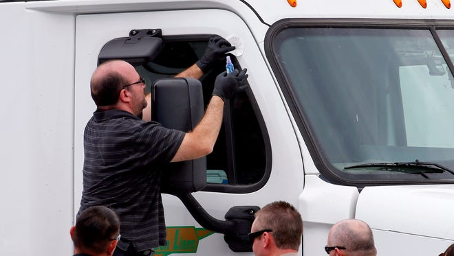 Arizona Department of Public Safety officers inspect a tractor trailer with a bullet hole in the passenger door shortly after it was shot near 67th Ave and I-10 on Sept. 10, 2015 in Phoenix.