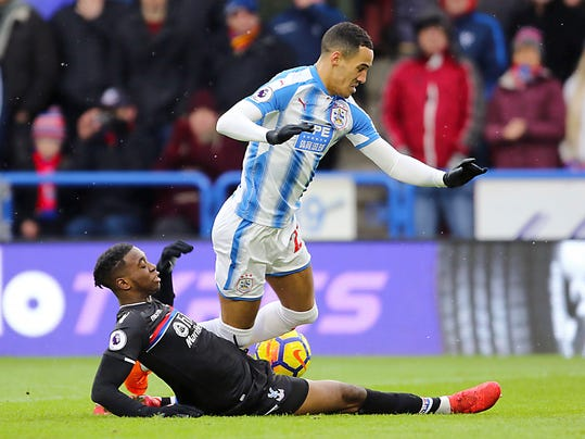 Crystal Palace's Jeffrey Schlupp, left, vies for the ball with Huddersfield Town's Tom Ince, during the English Premier League soccer match between Huddersfield and Crystal Palace at the John Smith's Stadium, in Huddersfield, England, Saturday March 17, 2018. (Richard Sellers/PA via AP)