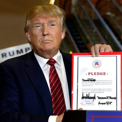 Donald Trump holds his GOP loyalty pledge during a