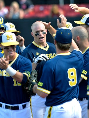 Michigan's Kendall Patrick, center, is congratulated by teammates following his two-run home run May 29, 2015, in Louisville Ky.