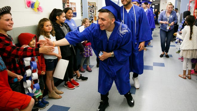 McNary High School senior Ramiro Garcia high-fives Kennedy Elementary School students during a Parade of Honor on Friday, June 1, 2018, in Keizer. The graduates returned to their elementary school for a parade in full cap and gown for current students.