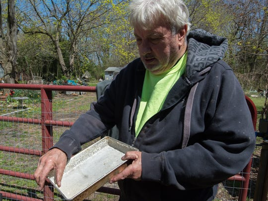 Zane Edwards of Milton holds a pan that he uses to feed his cats covered with salt residue from the water filtration system.  Clean Delaware had water filtration system installed on Zane's property after nitrate levels were found to be too high, in the farm areas where Clean Delaware sprays their waste.