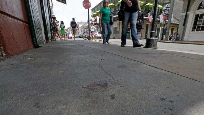 Blood stains are seen on the sidewalk at the scene of a shooting that happened early morning on Bourbon Street in New Orleans, June 29, 2014.