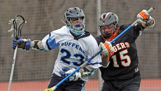 White Plains' David Ventura (15) defends Suffern's CJ Greco (23) during boys lacrosse game at Suffern Middle School on April 11, 2014.  Suffern defeated White Plains 11-9.
