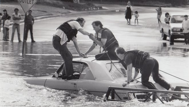 James Baker is helped out of his car by Rural-Metro firefighters Bob Bagwell and Jim Mack during a flood in Indian Bend Wash August 15, 1990.