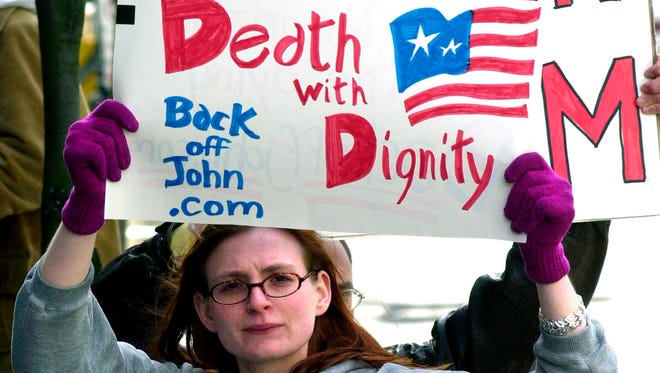Stacey Richter holds a sign outside a federal courthouse in Portland, Ore., as a hearing begins to decide the fate of Oregon's physician-assisted suicide law on March 22, 2002.