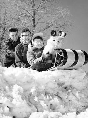 A family sleds on a toboggan in Milwaukee in 1956 (state archives image No. 7857).