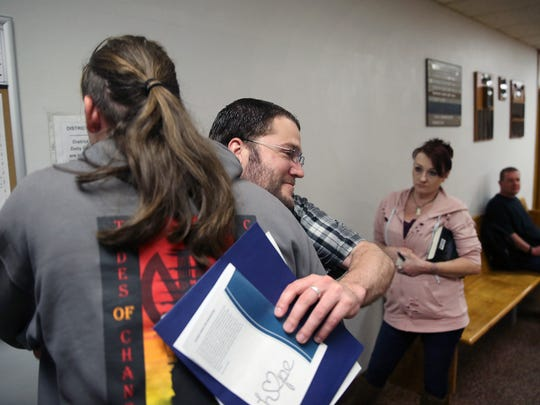 Nathan Hempel, center, gets a hug outside of Kitsap County District Court after he graduated from the behavioral health court diversion program.