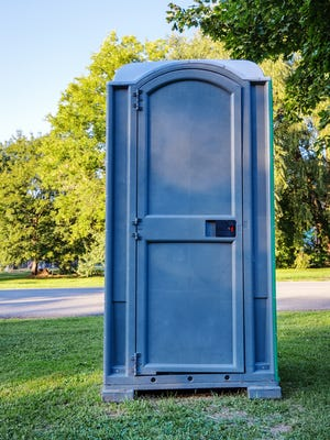 Single Blue Outhouse on Grass in Park