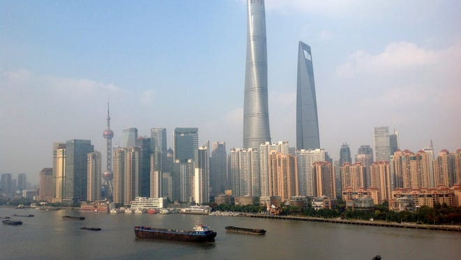 A symbol of Shanghai's new, financial strength in the world,  this collection of skyscrapers, including the Oriental Pearl (TV) Tower, were constructed in just the last 25 years in an area that used to be rice paddy fields. They are pictured here from The Bund, a riverfront area on the west bank of Huangpu River. Picture taken in Shanghai, China in November, 2014.