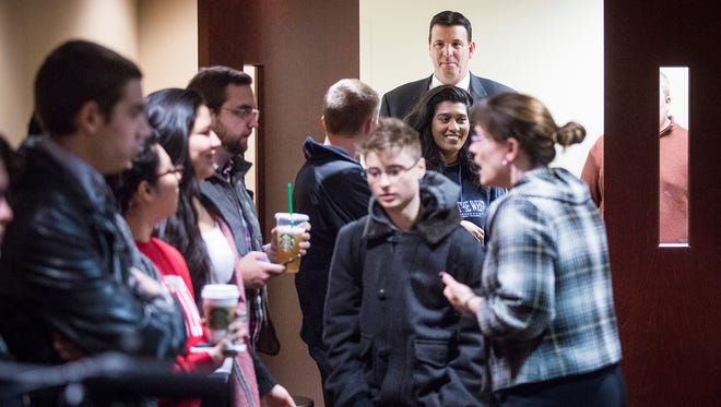 During a meeting in February, Rick Hall, chairman of the board of trustees at Ball State University, makes his way past students concerned about the resignation of President Paul Ferguson.