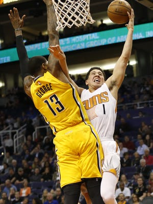 Phoenix Suns' Devin Booker is fouled by Indiana Pacers forward Paul George in the first quarter during NBA action at Talking Stick Resort Arena in Phoenix January 19, 2016.