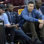 LSU freshman Ben Simmons (center) sits courtside at a Cavs game next to agent Rich Paul.