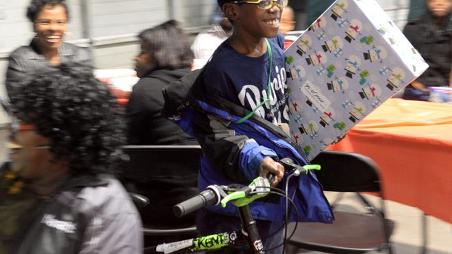Medjaisle Walker has a big smile on his face when he receives presents including a bike at the FTS International Christmas celebration Thursday afternoon.