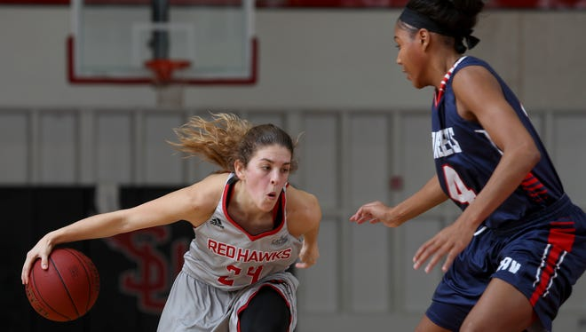 Simpson University's Esther Wofford takes the ball past University of Antelope Valley's Aujanay Chambers in the Redhawks' 81-55 loss on Thursday.