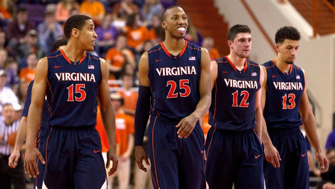 Virginia Cavaliers guard Malcolm Brogdon (15), forward Akil Mitchell (25), guard Joe Harris (12), and forward Anthony Gill (13) walk on the court during the second half against the Clemson Tigers at J.C. Littlejohn Coliseum. The Cavaliers won 63-58.