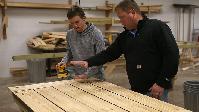 Lake View's Elliot Peterson listens to instructions from his teacher, Jory Wiemers , while working on a wooden table he built with a partner inside the Ag Department on Feb. 2, 2018.