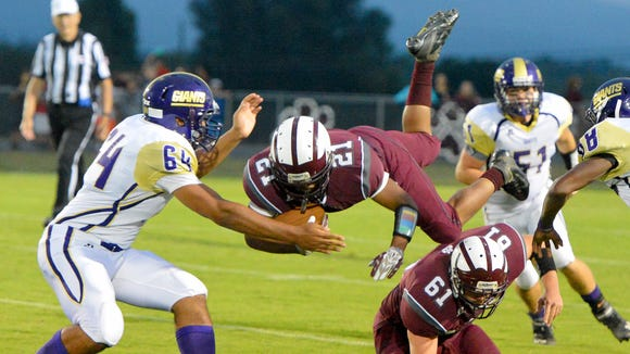 Stuarts Draft's Izzy Johnson leaps over teammate Andrew Fix as Waynesboro's K.K. Germany reaches for him during the first half of a football game played in Stuarts Draft on Friday, Sept. 12, 2014.