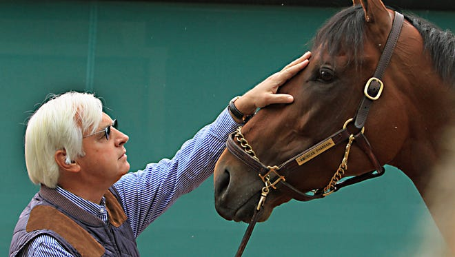 Trainer Bob Baffert rubs the head of Preakness Stakes winner American Pharoah outside the stakes barn, Sunday, May 17, 2015 at Pimlico Race Course in Baltimore.