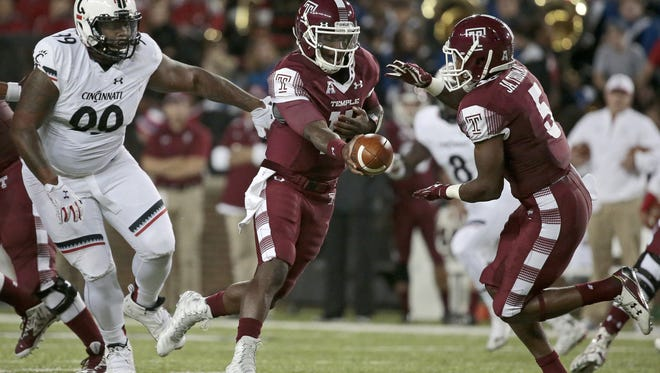 Temple quarterback P.J. Walker (11) hands off to running back Jahad Thomas (5) during the first quarter of the NCAA football game between the Cincinnati Bearcats and the Temple Owls at Nippert Stadium on the campus of the University of Cincinnati on Saturday, Sept. 12, 2015.