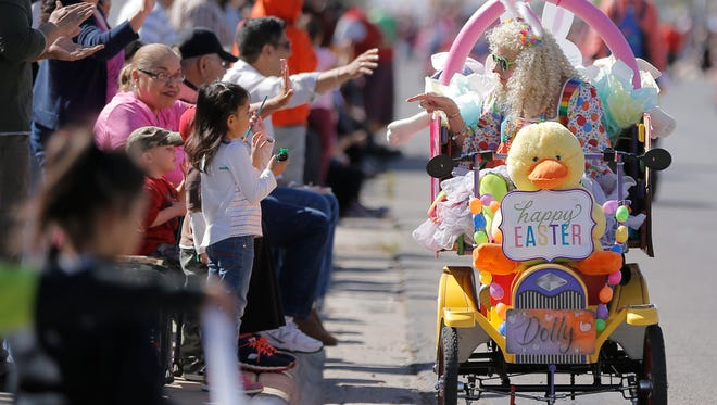 Dolly clowns around with children along the NorthEaster Parade route last year in Northeast El Paso.