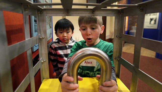 Ferber Elementary School students David Xiong, left, and Alex Brilowski experiment with the an interactive display during a visit to the Harry Houdini exhibit at the Museum at the Castle in Appleton.